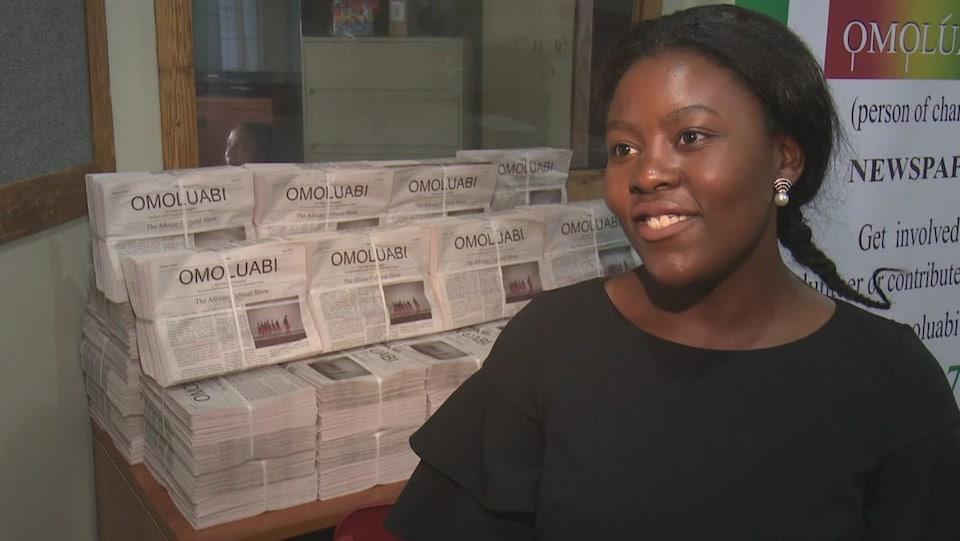 Joyce Kalinga se tient devant une pile de journaux.