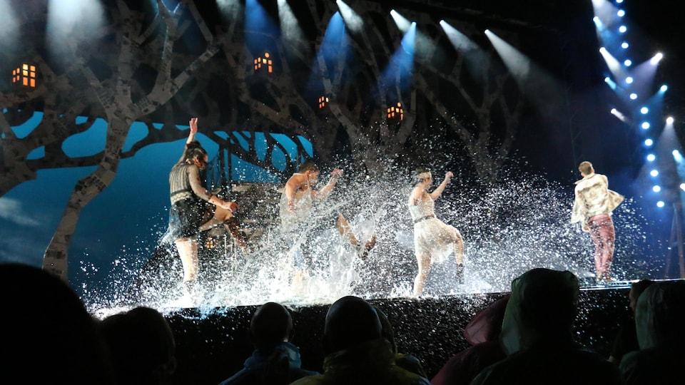 Des danseurs éclaboussent les spectateurs aux première rangées.