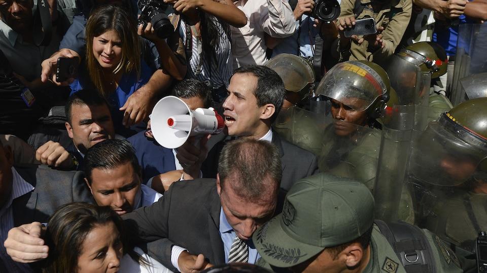Juan Guaido dans la rue, parle dans un microphone.