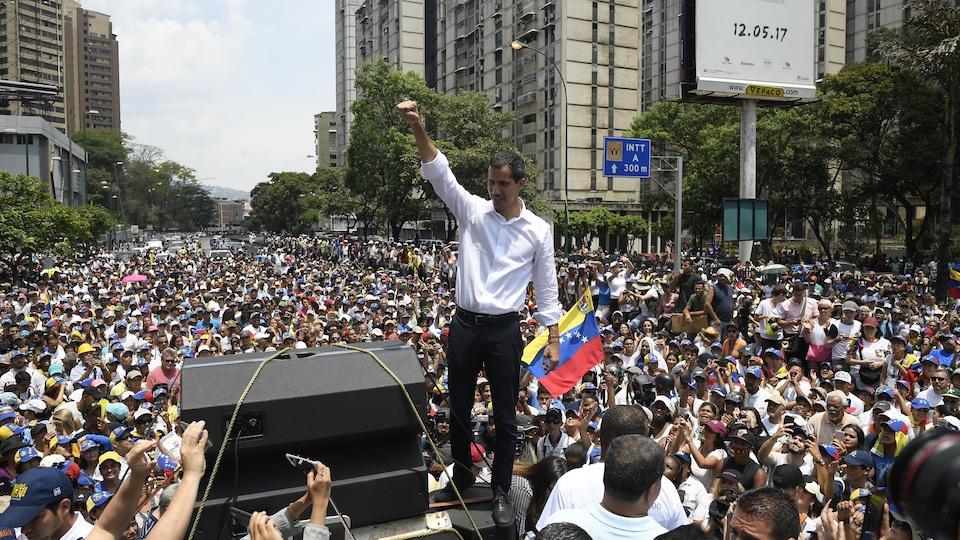 Juan Guaido lève un poing en l'air sur une petite tribune installée au milieu d'une foule de plusieurs centaines de personnes.