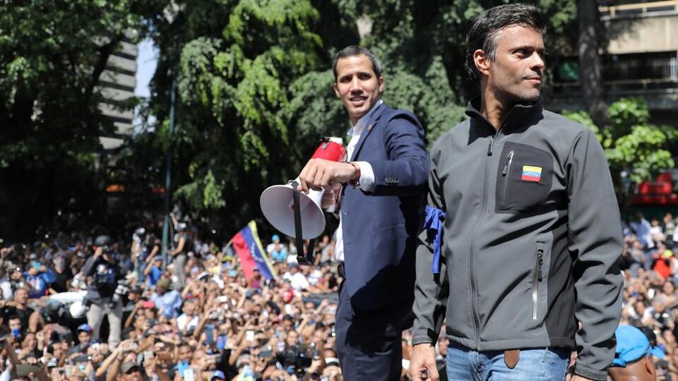 Deux hommes souriant, debout sur une plateforme, au milieu d'une foule, à l'extérieur.