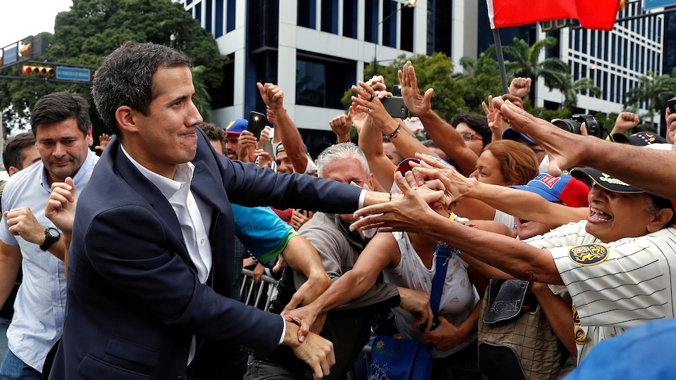 Juan Guaido salue ses partisans lors d'un rassemblement contre le gouvernement du président vénézuélien Nicolas Maduro, à Caracas, le 23 janvier 2019.