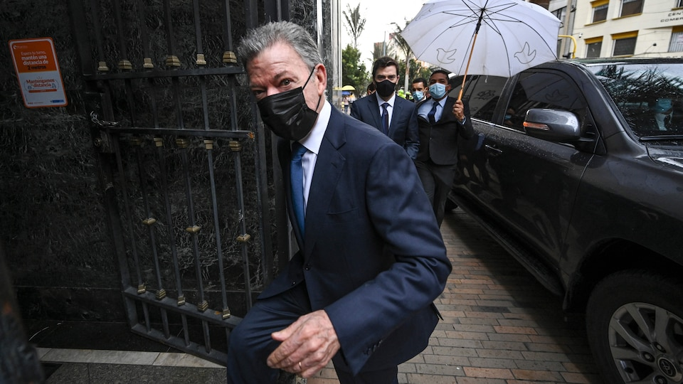 L'ancien président Juan Manuel Santos portant un masque et entrant dans un édifice.