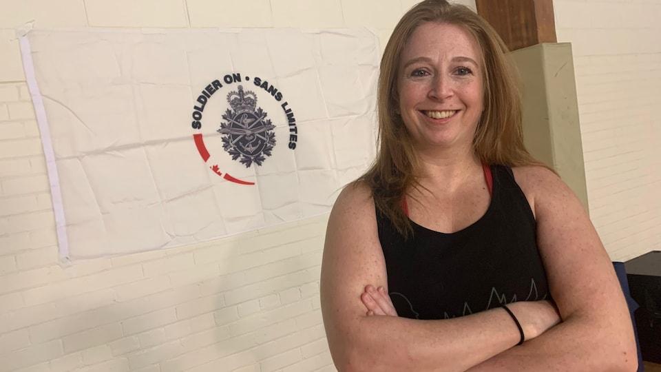 Une femme en habits de sport souriante, devant le drapeau du programme Sans limites.