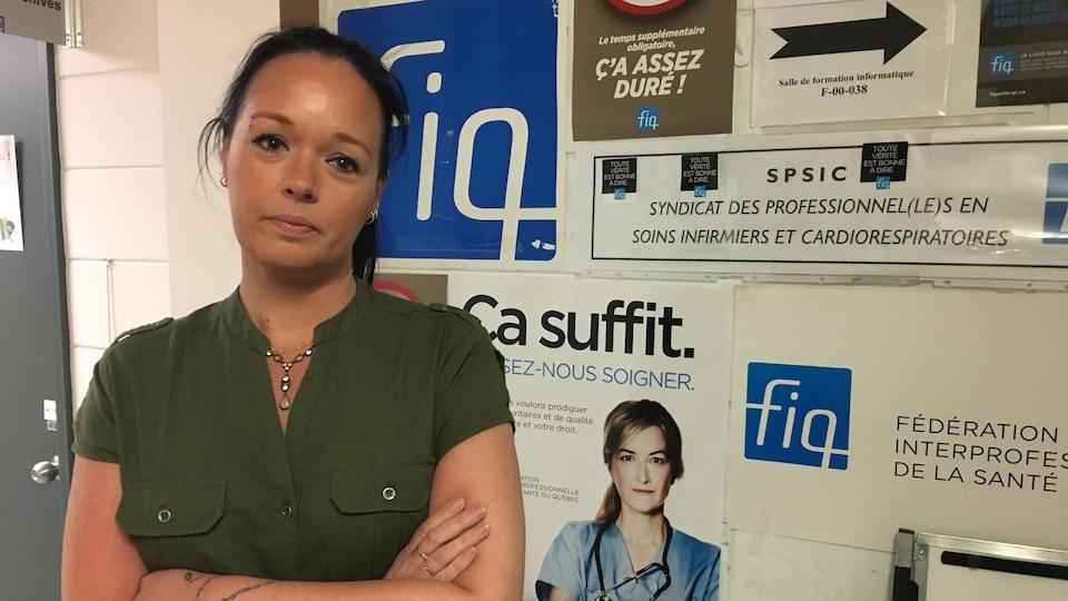 Julie Bouchard pose devant des affiches de la FIQ