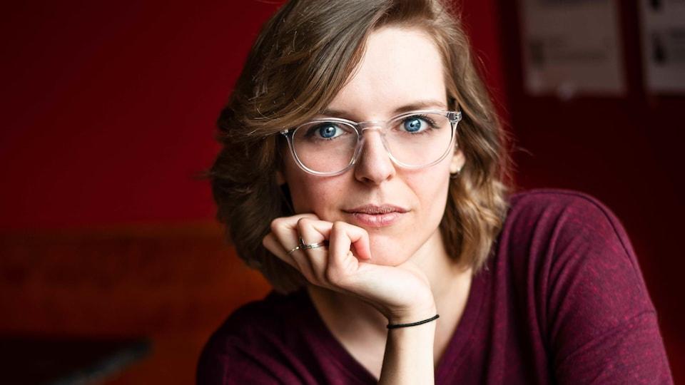 Portrait en couleur de l'autrice et humoriste Julie Day-Lebel, une main sous le menton. Elle porte des lunettes et un chandail à manches longues bordeaux.