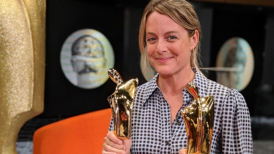 La comédienne tient deux statuettes dorées dans ses mains.