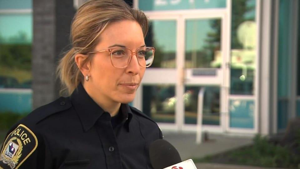 Julie Marois, porte-parole du Service de police de la Ville de Laval, parle aux médias devant un édifice.