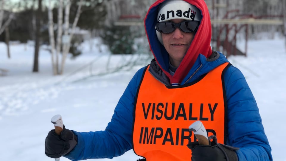 Julie Mayer avec son dossard Visually Impaired, son manteau d'hiver et ses skis de fond.