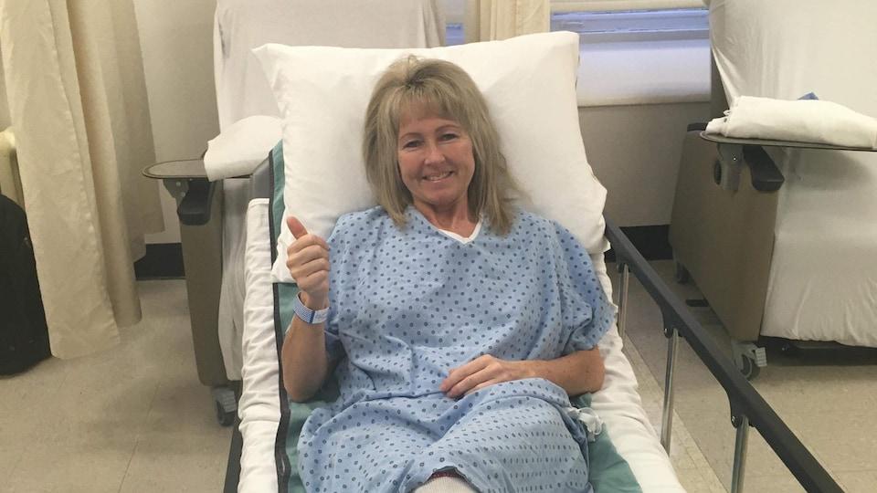 Une femme dans la quarantaine d'année repose dans un lit d'hôpital habillée d'une jaquette.