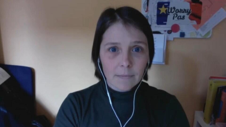 Une femme avec des écouteurs dans regarde l'écran pendant une entrevue via l'ordinateur.