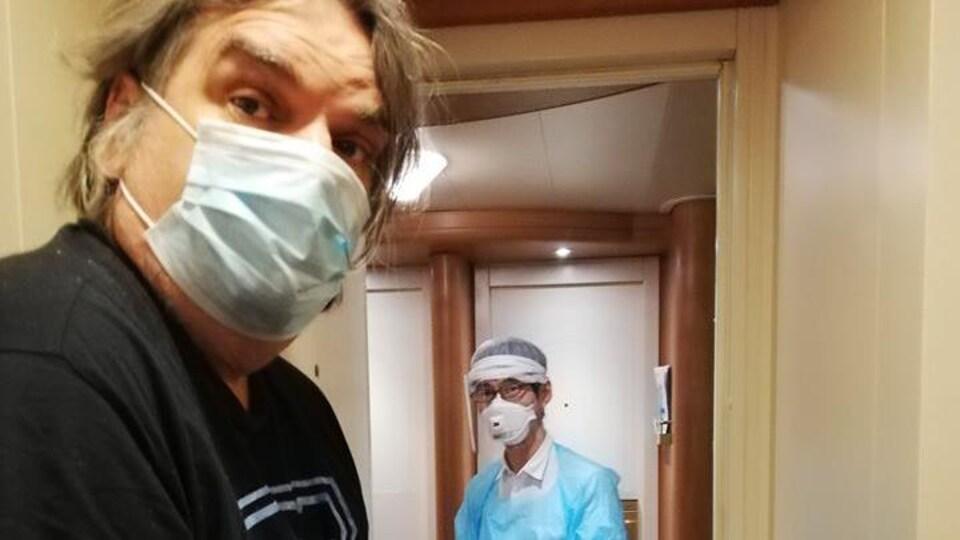 Julien Bergeron, un masque sur la bouche, s'apprête à quitter sa chambre. Un Japonais l'attend près de la porte.