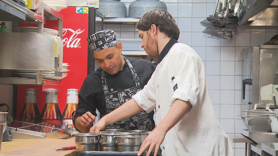 Julios Caesar avec un autre employé qui lui montre des plats