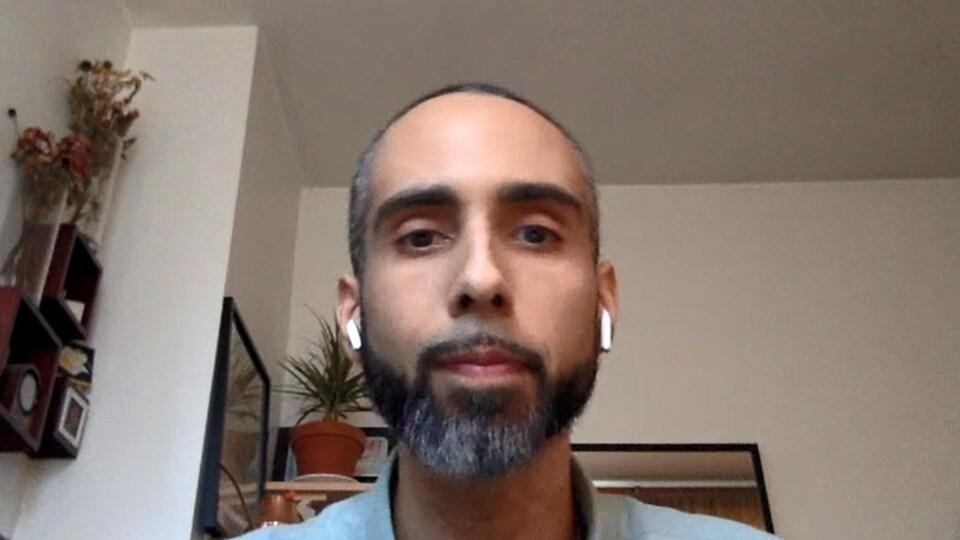 Un homme portant des écouteurs sans fils, en entrevue par vidéoconférence.