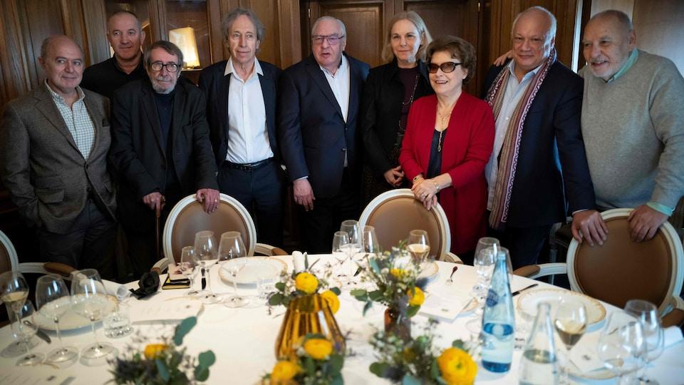 Les neuf personnes sont debout derrière une table et posent pour la photo.