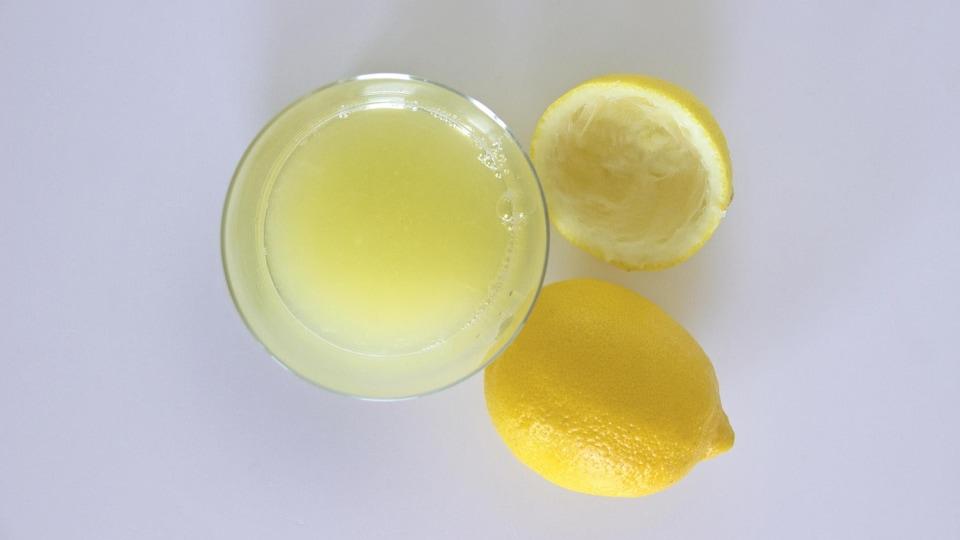 Un verre de jus de citron et un citron pressé.