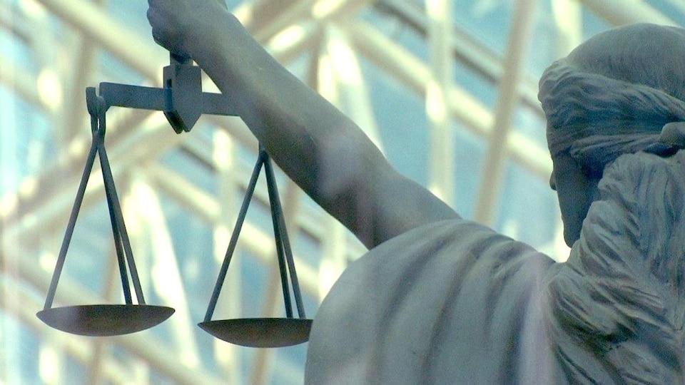 Photo d'une statue représentant la justice, prise de dos. Elle tient une balance à bout de bras et ses yeux sont bandés. En arrière-plan se trouve une structure métallique ensoleillée.