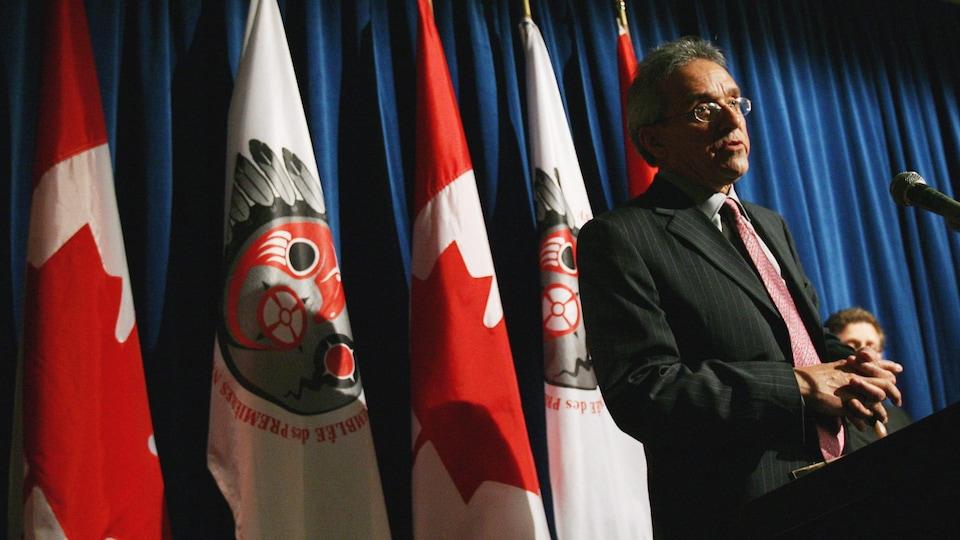 Il est à un podium lors d'une conférence de presse.