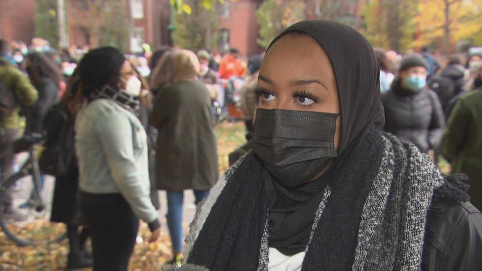 Mme Yusuf en entrevue, dans une parc avec des dizaines de personnes derrière elle.