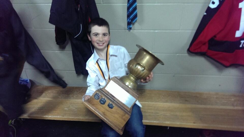 Petit garçon tenant gros trophée.