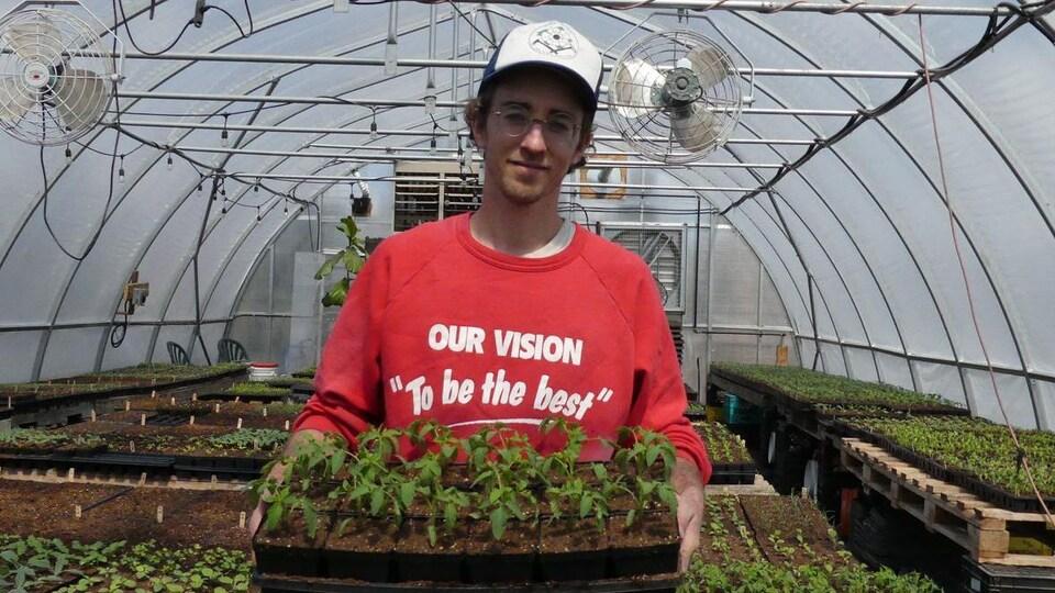 Un homme dans une serre avec des plantes dans les mains.