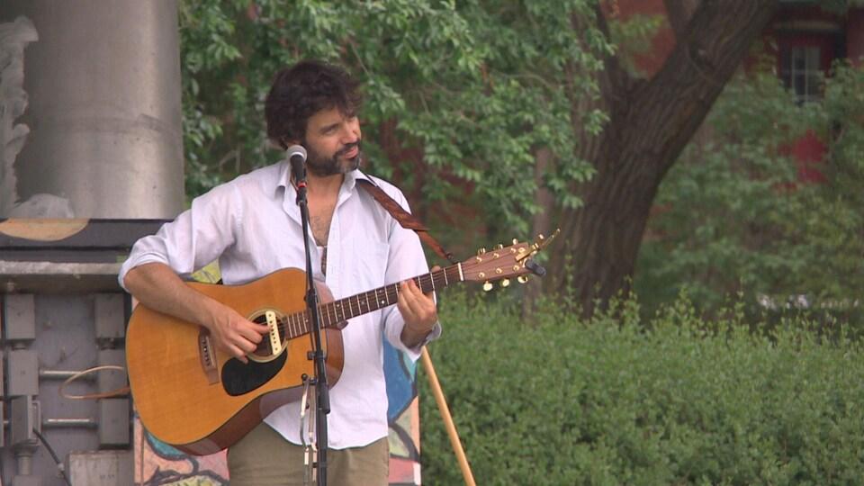 Un homme joue de la guitare dans un parc.