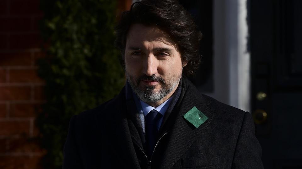 Le premier ministre du Canada se dirigeant vers le micro, à l'extérieur.