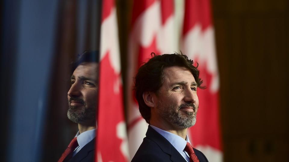 Justin Trudeau souriant devant un drapeau du Canada.