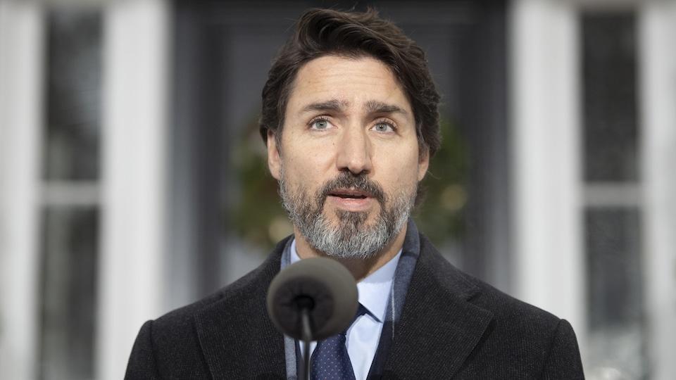 Justin Trudeau, debout à l'extérieur et derrière un micro pour une conférence de presse.