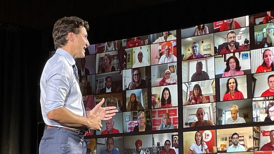 Justin Trudeau devant un grand écran montrant plusieurs partisans qui écoutent.