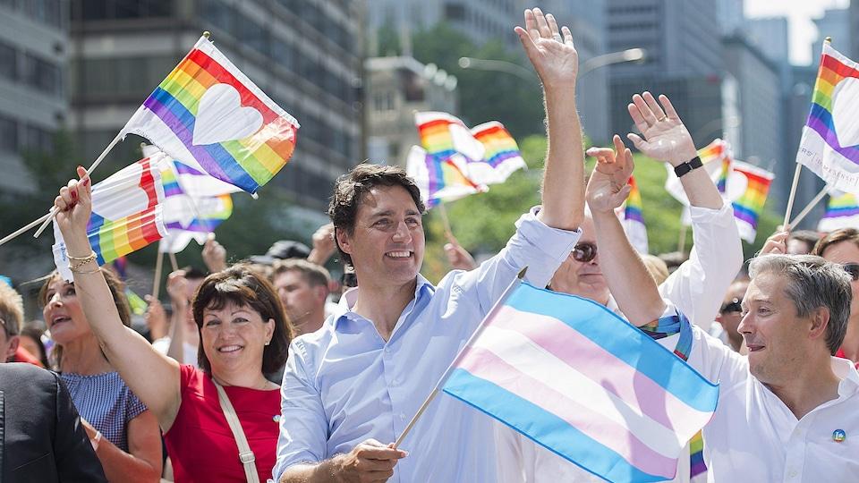 Le premier ministre canadien Justin Trudeau prend part au défilé de Fierté Montréal, un drapeau de la fierté transgenre à la main.