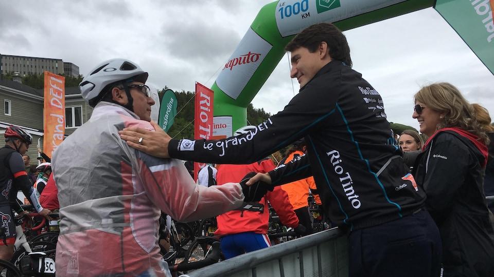Justin Trudeau serre la main d'un cycliste.