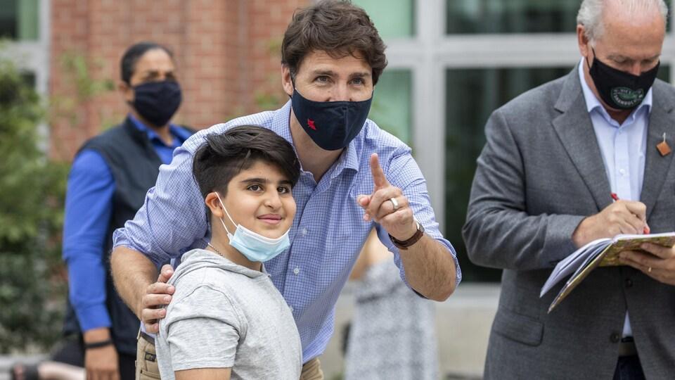 Justin Trudeau, en compagnie de John Horgan, parle à un garçon.