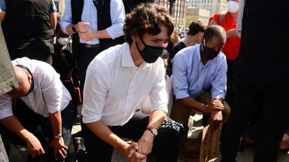 Justin Trudeau, un genou par terre, au milieu d'une foule.
