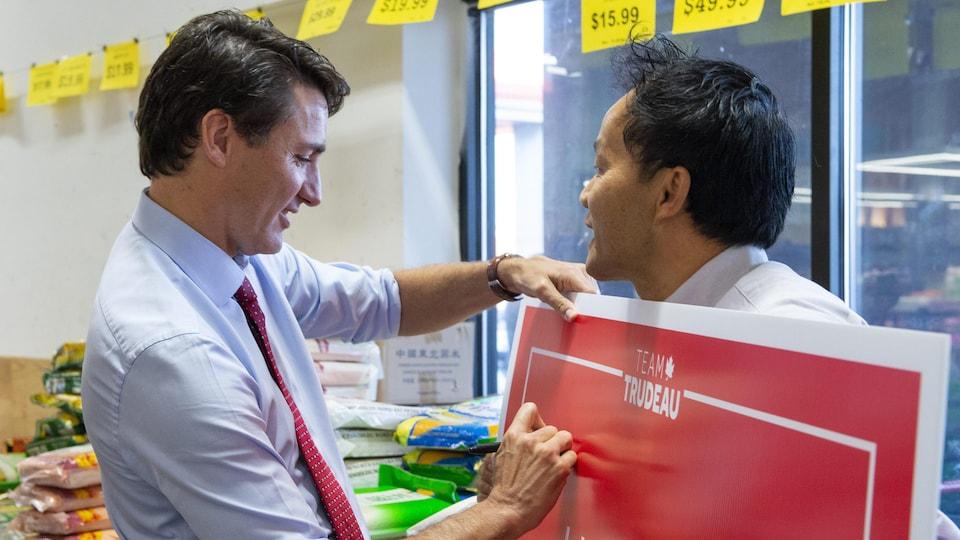 Justin Trudeau signe la pancarte électorale qu'un homme tient dans ses mains.