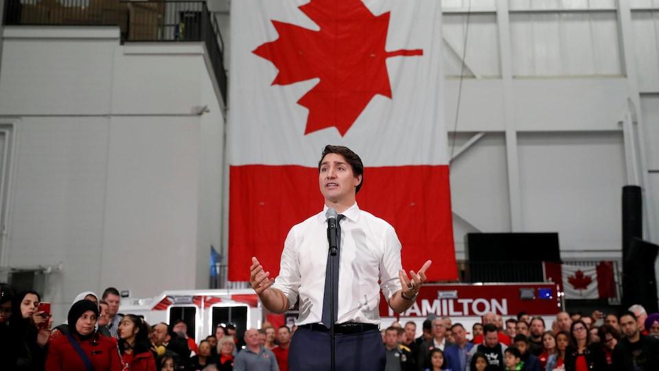 Justin Trudeau parle devant une foule dans une caserne de pompiers.