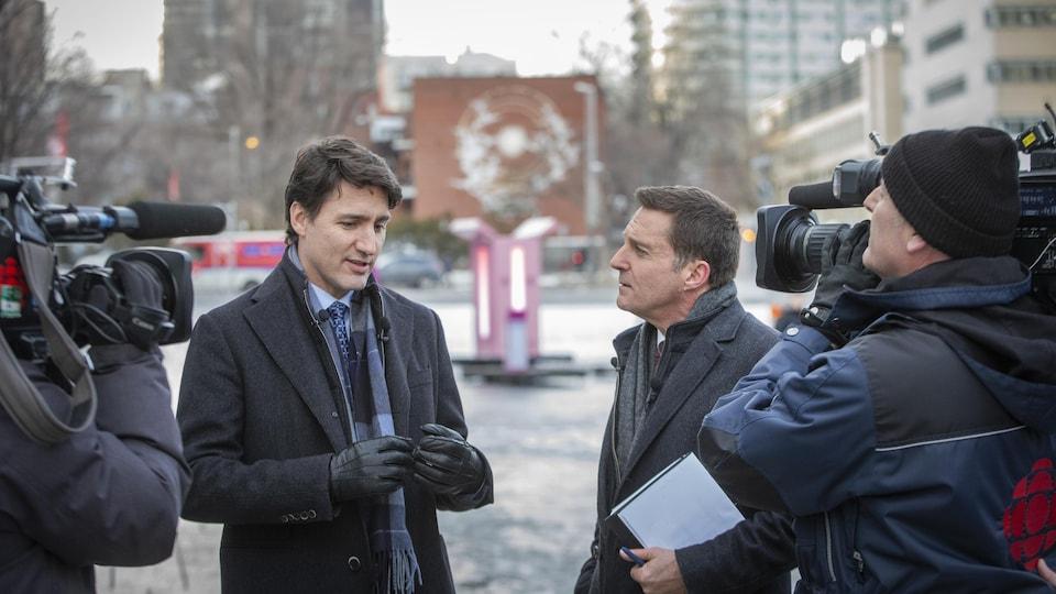 Les deux hommes discutent devant des caméras dans le centre-ville de Montréal.