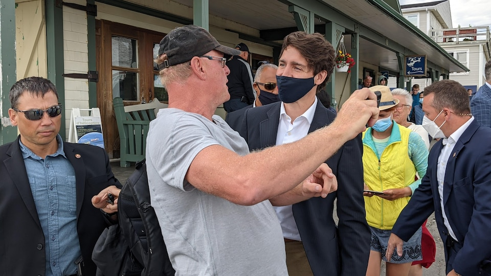 Justin Trudeau stands next to a man handing over his cell phone, ready to take a picture.