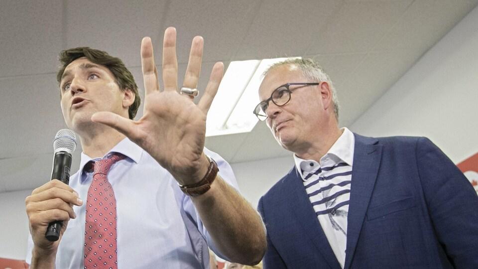 Justin Trudeau parle dans un micro, Réjean Hébert le regarde.