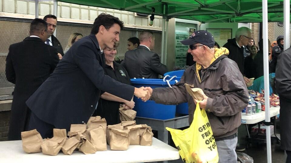 Justin Trudeau serrant la même d'un homme.
