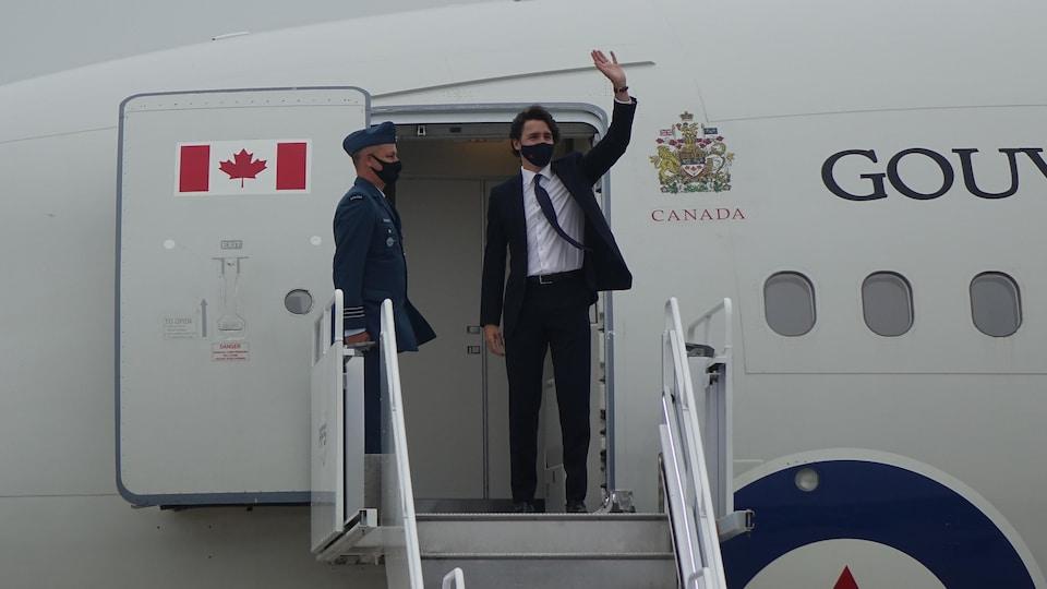 Justin Trudeau fait un salut de la main du haut de l'escalier menant à la porte de l'avion.