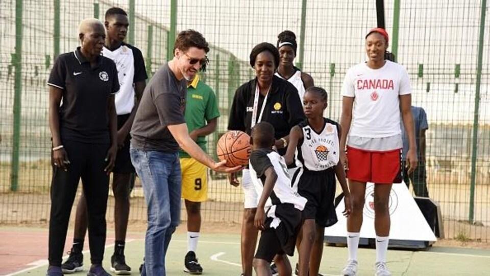 Il joue au basketball avec des enfants lors de la cérémonie de signature d'un accord entre les comités olympiques du Canada et du Sénégal à Dakar le 12 février 2020.