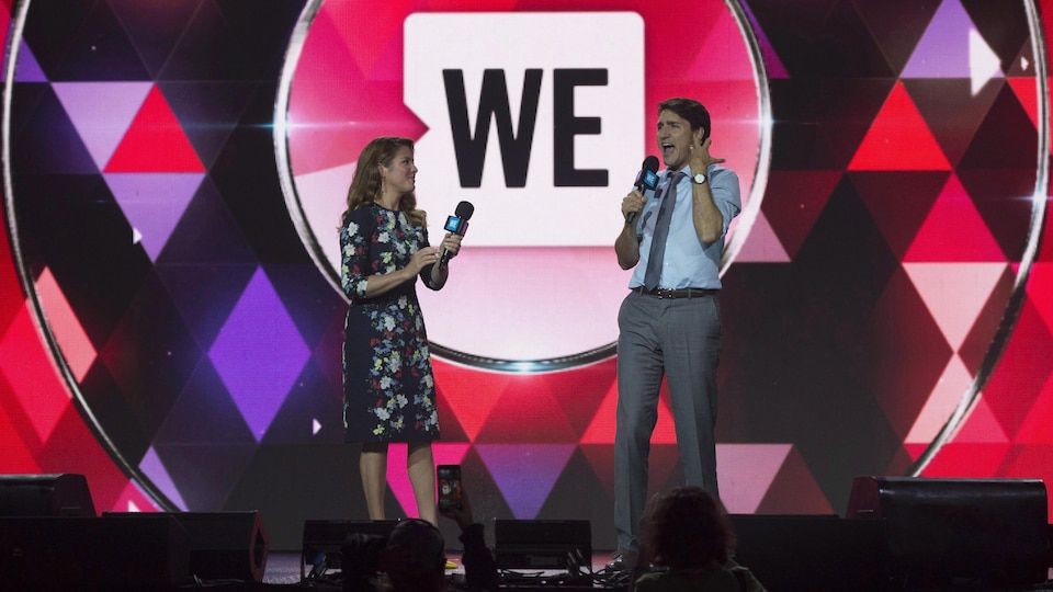 Justin Trudeau et Sophie Grégoire seuls sur scène devant un logo de WE Charity