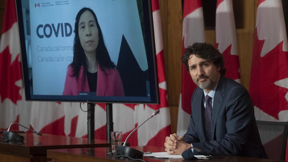 Le premier ministre Justin Trudeau et, sur un écran de télévision, l'administratrice en chef de la santé publique, la Dre Theresa Tam.