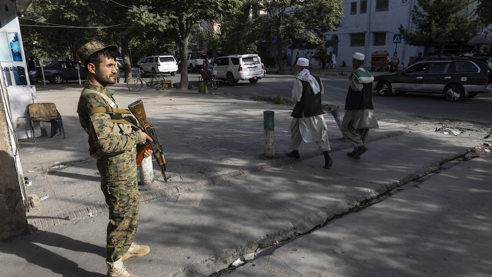 Un policier afghan armé et deux autres hommes à Kabou, le 13 août 2021.