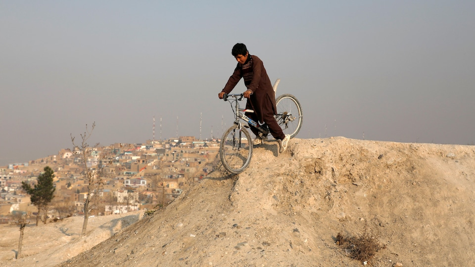 Un garçon fait de la bicyclette.