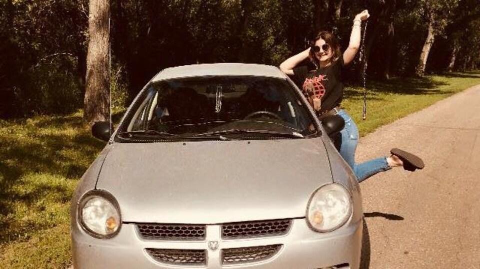 Kailynn Bursic-Panchuk pose à côté de sa voiture sur une route rurale ensoleillée.