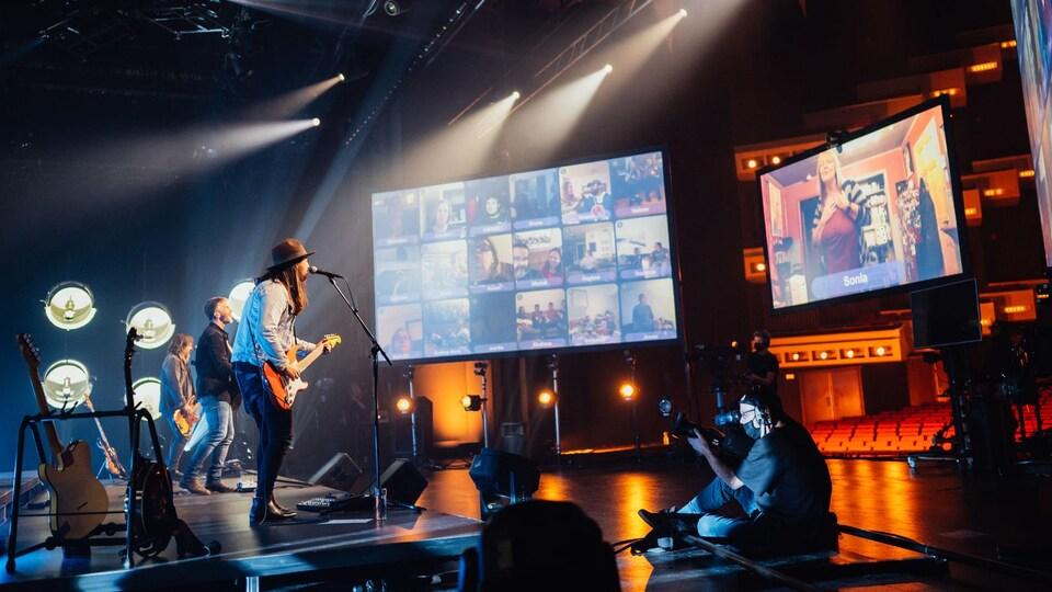 Un groupe de musique joue devant des écrans.