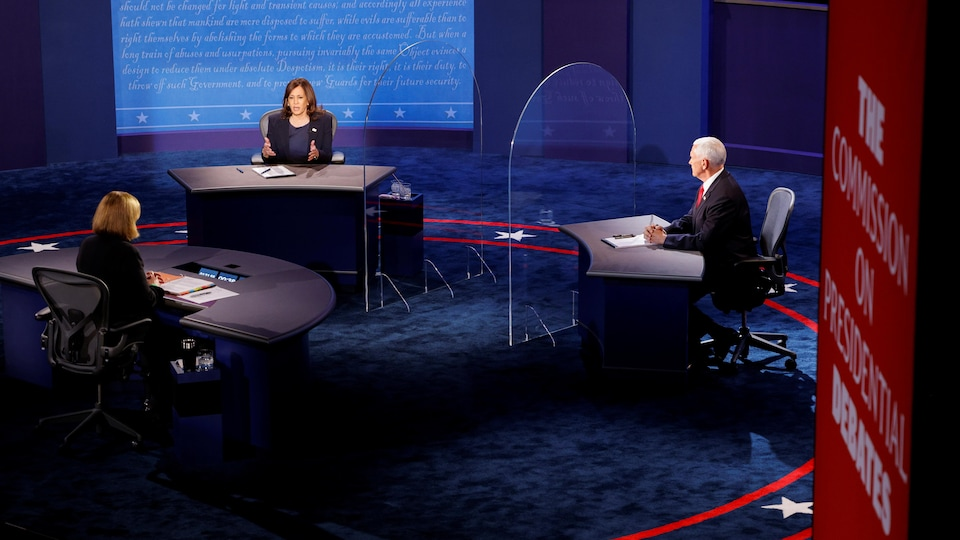 Les deux candidats sont assis devant la modératrice.