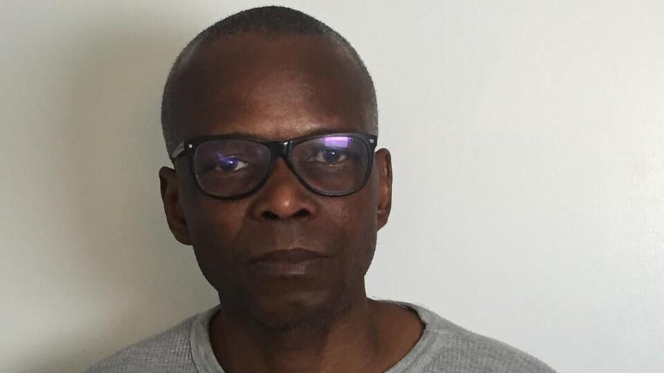 Un homme avec des lunettes pose pour la caméra.